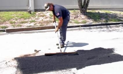 A worker repairing damaged asphalt