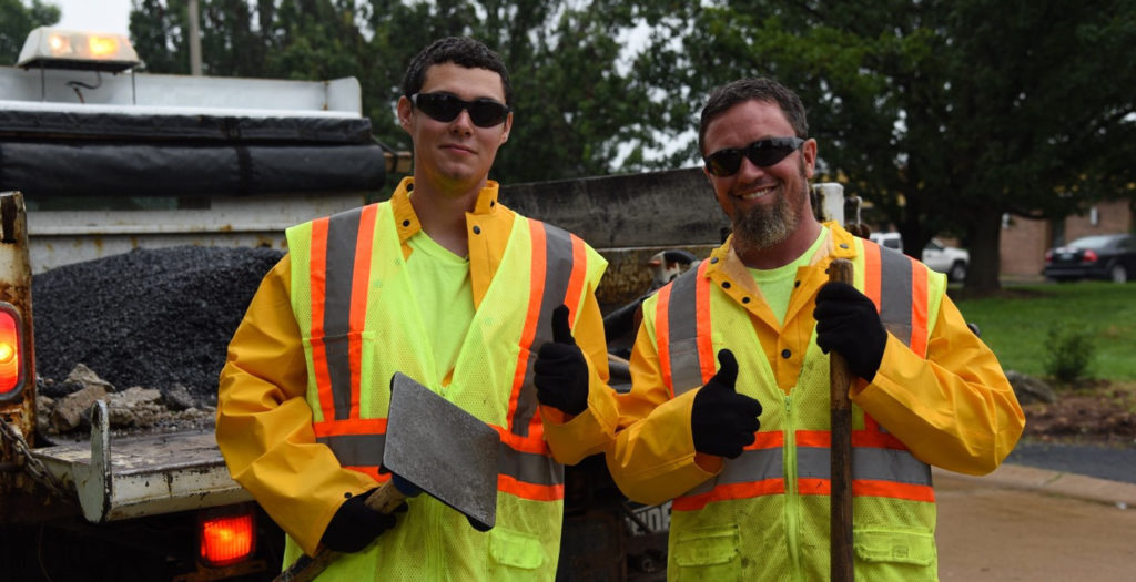 Two Duval Asphalt workers give a thumbs-up.