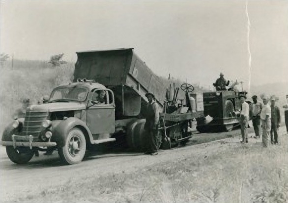 Workers laying asphalt over 50 years ago
