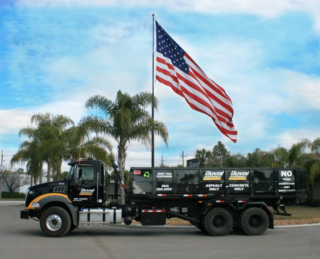 A truck carrying a roll-off container in front of the american flag.