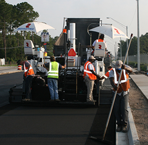 Workers laying down fresh asphalt