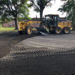 Fresh asphalt is laid out for the basketball court
