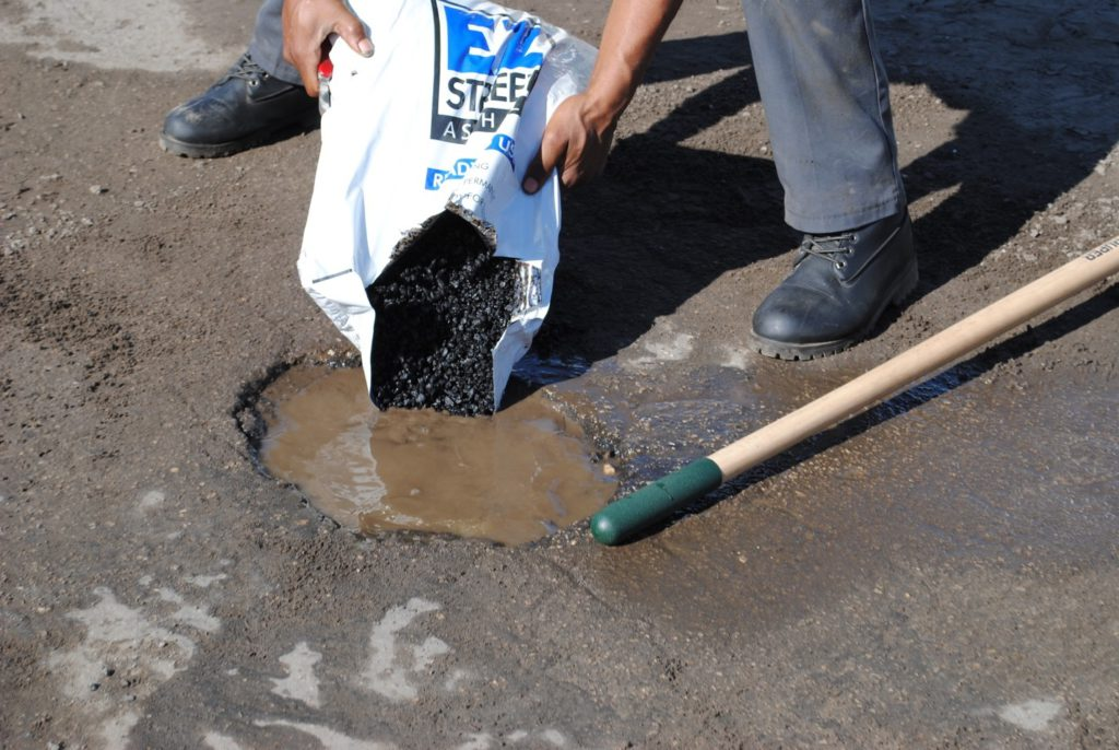 A worker pours EZ Street asphalt into a pothole