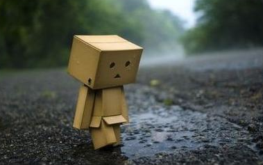 A sad cardboard robot standing in the rain.