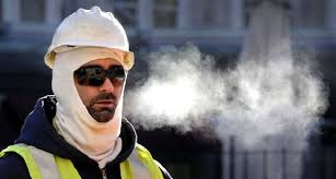 A worker's breath is visible as he works in the cold.