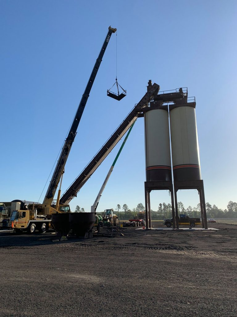 Picture shows new asphalt production plant construction. Two asphalt silos in early morning light, showing a construction crane attaching conveyor belts to the silos.