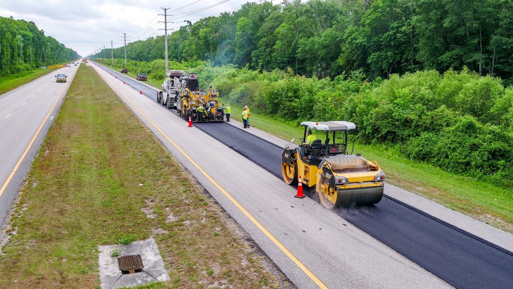 The photo shows an image of the paving train, including a steel wheeler roller and asphalt paver, paving US 1 southbound in St. Johns County, FL.
